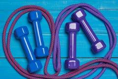 Deux paires de gantelae sur les conseils, le bleu et les haltères bleus de lilas et autour de corde à sauter lilas et rose, sport Images libres de droits