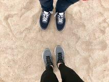 Deux paires de jambes dans des chaussures d'espadrilles se tiennent vis-à-vis de l'un l'autre contre le sable chaud d'or jaune lâ images stock
