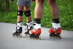 Deux paires de jambes sur des patins de rouleau Image stock