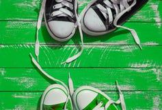 Deux paires de la jeunesse d'espadrilles avec les dentelles déliées sur le surfa vert Image libre de droits
