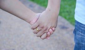 Deux paires de mains dans l'amour lient tendrement Images stock