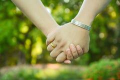 Deux paires de mains dans l'amour lient tendrement Photographie stock