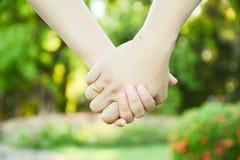 Deux paires de mains dans l'amour lient tendrement Photo libre de droits