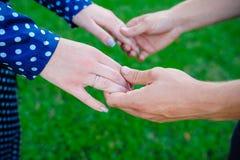 Deux paires de mains dans l'amour lient tendrement sur le fond d'herbe verte Photographie stock