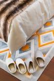 Deux paires de pantoufles blanches sur le tapis près d'un lit image libre de droits