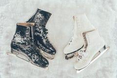 Deux paires de patins blancs et noirs sur la neige photos stock