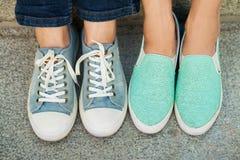 Deux paires de pieds du ` s de fille dans des espadrilles photographie stock