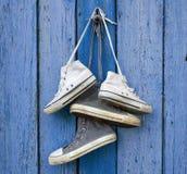 Deux paires de vieilles espadrilles usées de textile accrochent sur un clou photographie stock