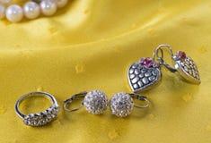 Deux paires des boucles d'oreille et de l'anneau sur le jaune Photographie stock libre de droits