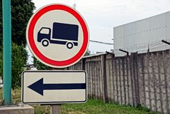 Deux panneaux routiers près de la route près d'une barrière grise avec le barbelé Images stock