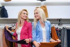Deux pantalons convenables blonds d'achats d'achats de femme, boutique de sourire heureuse de mode de clientes de filles choisiss Photographie stock libre de droits
