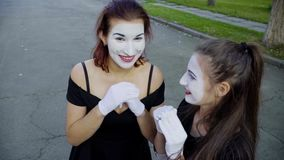 Deux pantomimes de filles imitent l'embarras quand voir l'appareil-photo banque de vidéos