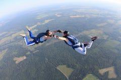 Deux parachutistes dans le T-shirts rayé volent dans le ciel photos stock