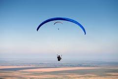 Deux parapentistes en vol au-dessus de la terre Image stock