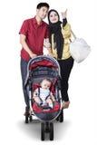 Deux parents avec le bébé dans la poussette Photo stock
