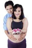 Deux parents montrant des chaussures pour le bébé Image libre de droits