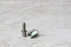 Deux parts d'attache de rivet de bruit en métal sur le fond gris de ciment Horizontal avec l'espace de copie pour le texte et la  photos libres de droits