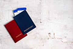 Deux passeports de voyageurs rouges et bleus avec des cartes d'embarquement pour l'avion concept de course photos stock