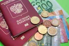 Deux passeports et notes étrangers russes d'euro de diverses dénominations et d'Eurocent sur un clpse vert de fond  images libres de droits