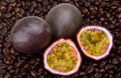 Deux passiflores comestibles de passiflore et deux moitiés avec les graines juteuses mûres dans la perspective du café rôti parfu photographie stock libre de droits