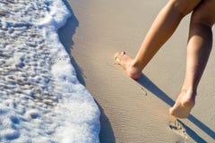 Deux pattes de femmes marchant sur la plage de sable Image stock