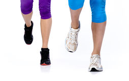 Deux pattes de la femme fonctionnant sur un fond blanc images stock