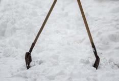 Deux pelles coincées à la banque de la neige Photographie stock libre de droits