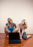 Deux penser d'amis et d'ordinateur portatif Photos stock
