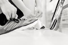 Deux personnes attachant leurs chaussures avant un jeu de tennis Photographie stock