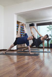 Deux personnes avec des jambes augmentées et arment tendu faisant le yoga dans un studio de yoga Image libre de droits