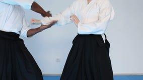 Deux personnes dans le hakama noir pratiquent l'Aikido sur la formation d'arts martiaux banque de vidéos
