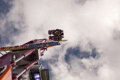 Deux personnes dans un panier à l'envers avec le ciel à l'arrière-plan sur un amusement mettent en place Images stock
