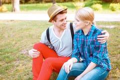 Deux personnes de embrassement s'asseyant sur l'herbe en parc Photos libres de droits