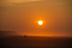 Deux personnes de pair sur la plage au coucher du soleil Photographie stock