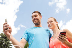 Deux personnes de sourire avec des smartphones dehors Photo libre de droits