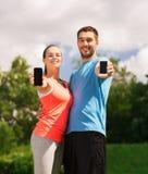 Deux personnes de sourire avec des smartphones dehors Photographie stock