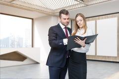 Deux personnes discutant des questions de travail dans le lobby de bureau Image stock