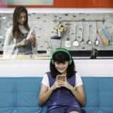 Deux personnes, fille jouant et regardant le smartphone tandis que mère faisant cuire la nourriture pour elle Images stock