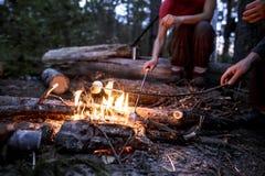 Deux personnes font frire le marshmeloo à l'enjeu sur une colonie de vacances Photo stock