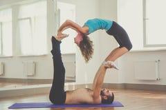 Deux personnes font l'acro-yoga à l'intérieur Image stock