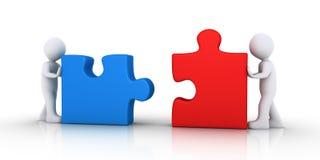 Deux personnes joignent les morceaux de puzzle Photographie stock libre de droits