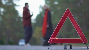 Deux personnes jurent sur un fond de triangle de avertissement Silhouette des couples de serment Foyer sur le signe de voiture banque de vidéos