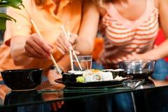 Deux personnes mangeant des sushi Images stock