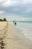 Deux personnes marchant à partir du visualisateur le long de la plage Photographie stock libre de droits