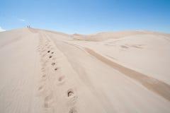 Deux personnes marchant au-dessus des dunes de sable Photo libre de droits