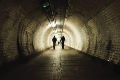 Deux personnes marchant dans le tunnel Image stock