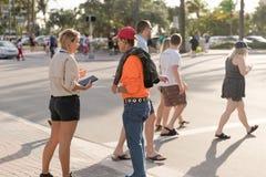 Deux personnes parlant sur la rue, femme tenant le comprimé dans des mains Photos stock