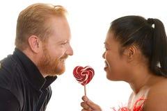 Deux personnes partagent une sucrerie Image stock