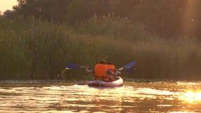 Deux personnes ramant des avirons se reposant dans un kayak sur le lac dans le coucher du soleil banque de vidéos