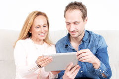 Deux personnes regardant l'appareil électronique Photos stock